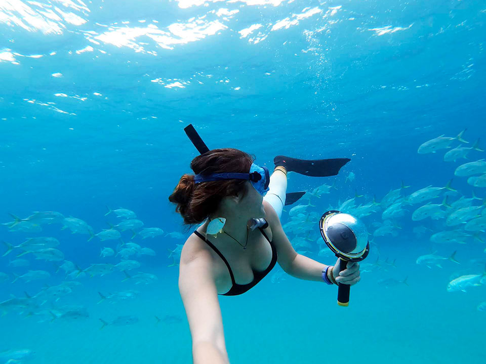 Girl snorkeling with a school of Jack Sig Fish