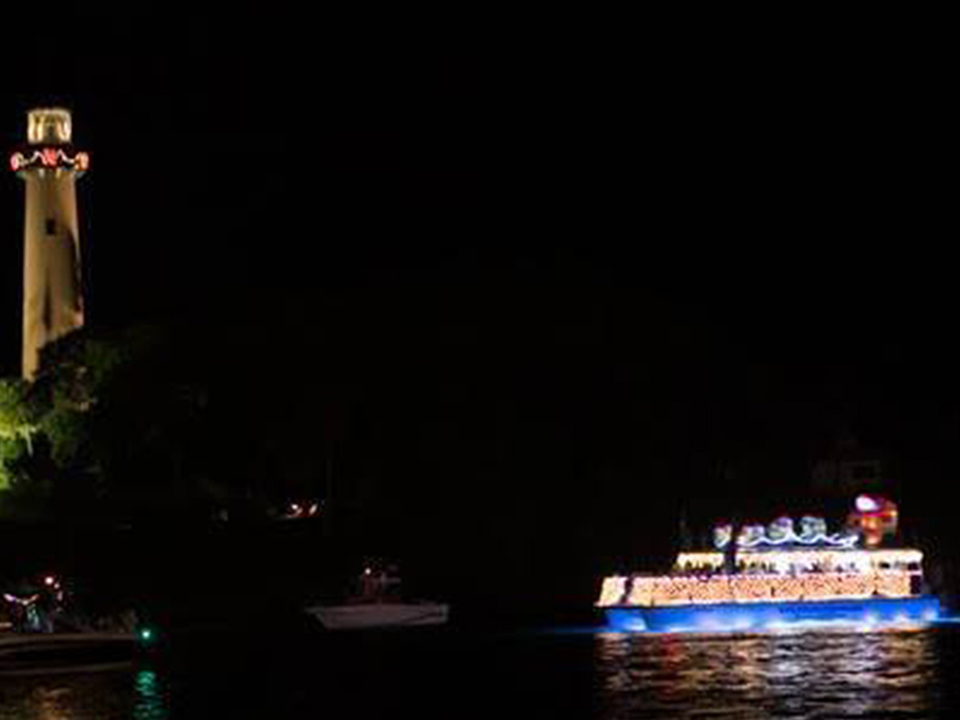 Manatee Queen pontoon with Christmas light passing Jupiter Island lighthouse